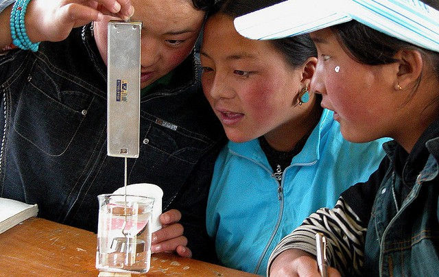 Grade 7 students conducting experiments on displacement during Science class, Kangding, Sichuan China